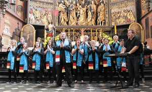 Father Krzysztof Wtorek with his international Gospel-Rock group sing in front of the altar of Wita Stwosza (Saint Mary's altar) at St. Mary's Basilica in Krakow, Poland last year. The altar is the largest Gothic altarpiece in the world, and a national treasure in Poland. Father Wtorek, parochial vicar at Holy Trinity Parish in Margate, and his group will perform at World Youth Day in July. Photo by Ekkehard Heim