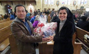 Sister Rosa Maria Ojeda, principal of Saint Peter School, Merchantville, presents Catholic Charities' Refugee case manager aide Hting Mangshang with a ceremonial basket of the donated items.