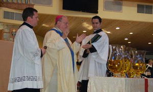 Above, Bishop Sullivan, with Father Michael Romano and seminarian Paul Abbruscato, blesses the holy oils and chrism at Our Lady of Hope Parish on March 22, during the diocese's Chrism Mass in Blackwood. Below, Bishop Sullivan incenses the altar of repose after the Mass of the Lord's Supper on Holy Thursday, March 24, at Our Lady Star of the Sea in Cape May. Photos by James A. McBride