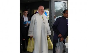 Above, Bishop Dennis Sullivan carries bags to be shipped to food pantries, after celebrating Mass at Saints Peter and Paul in Turnersville March 6 to kick off the Camden Diocese's FaithFULL initiative. Below, bags of donated items below a stained-glass rendition of the Last Supper. Photos by James A. McBride