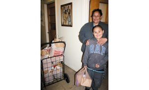 """A family receives food and frozen """"Plates for Christ"""" meals from Catholic Charities' food pantry in Atlantic City. Photo by Joanna Garnder"""