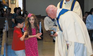Anthony and Angelina Bongiovanni present the offertory gifts to Father Robert Hughes, Vicar General, during the Autism Awareness Mass last Sunday afternoon at Church of the Holy Family in Sewell. Father Hughes was celebrant of the liturgy, which took place during Autism Awareness Month. Photo by James A. McBride