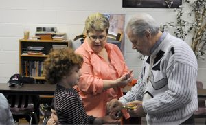 Kim and Jim Forte show Gavin how to receive Communion during religious education class for children with special needs at Our Lady of Hope Parish, Blackwood. Photo by Carl Peters