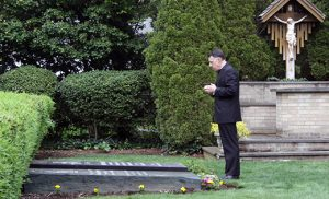 Bishop James F. Checchio prays at the graves of deceased bishops of Metuchen before evening prayer at the Cathedral of Saint Francis of Assisi, Metuchen, on May 2. Left Bishop Checchio processes into the cathedral. The next day, May 3, he was installed as the fifth bishop of the diocese in the Church of the Sacred Heart, South Plainfield.