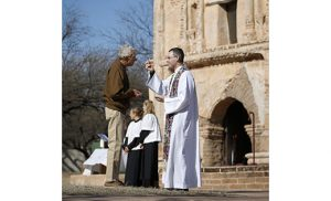 Jesuit Father Sean Carroll gives Communion during Mass at Tumacacori National Historical Park in Tumacacori, Ariz., Jan. 10. The service was part of the park's Kino Legacy Day, paying homage to Father Eusebio Francisco Kino and his contributions to the Pimeria Alta region, now northern Sonora, Mexico, and southern Arizona. Father Carroll is director of the Kino Border Initiative, a binational organization serving and advocating for migrants. CNS photo/Nancy Wiechec