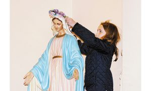 Cassidy Costello, 7, crowns a statue of Mary May 6 at Holy Child Parish, Runnemede. During the month of May many parishes and schools conduct Marian devotions. Photo by Alan M. Dumoff