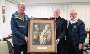 Representing the New Jersey State Knights of Columbus, Reggie Beckett, left, Vice Supreme Master of the Fourth Degree, and Andy Lipenta, Immediate Past State Deputy, present a painting of the Holy Family by 18th century artist Giovanni Balestra to Bishop Dennis Sullivan in the Camden Diocesan Center on May 10. Photo by James A. McBride