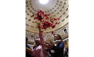 Women toss rose petals after Rome firefighters dropped the petals from the oculus of the Pantheon at the conclusion of Pentecost Mass May 15. The rose petals symbolize the tongues of fire that came upon the apostles at Pentecost. (CNS photo/Paul Haring)