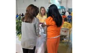 Prison ministry volunteers from the Church of St. Andrew the Apostle in Gibbsboro wash the hands of an inmate during a Holy Thursday Mass in 2015. With her back turned is volunteer Chris Parry, facing the inmate is volunteer Catherine Rossignol. Photo by Joanna Gardner