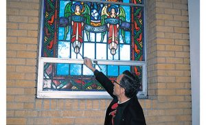 Father Joseph Capella, pastor of the Shrine of Our Lady of Guadalupe in Lindenwold, shows stained glass angels' feet that were repaired after damage done to them last January.  Photo by Peter G. Sánchez