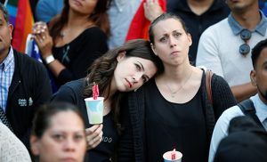 Women hold candles during a June 13 vigil in Los Angeles for the victims of the mass shooting at the Pulse gay nightclub in Orlando, Fla. A lone gunman, pledging allegiance to the Islamic State terrorist group, killed 49 people early June 12 at the nightclub. CNS photo/Lucy Nicholson, Reuters