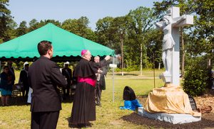 Bishop Dennis Sullivan and Father Michael Romano listen as South Jersey Catholic Cemeteries director Marianne Linka speaks at the dedication ceremony at the newly expanded Gate of Heaven Cemetery in Berlin on June 22. Below, the bishop blesses a crucifix on the grounds.