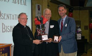 "Bishop Dennis Sullivan presents the Bishop's Cup for Outstanding Achievement to Deacon Frank Crossen and Patrick Healy of Saint Mary Parish, Gloucester City, at the House of Charity Final Report Meeting, held June 28 at Saint Charles Borromeo Parish, Sicklerville. Formerly struggling to meet the parish goal, Msgr. William Hodge, pastor, and the parish team worked with the House of Charity Office. As a result, the parish exceeded its 2015 goal and is doing well with its current campaign. The Final Report meeting ""was all about saluting our volunteer teams and clergy who truly allow the works of mercy to be accomplished throughout our diocese,"" said Sheila McGirl, associate director, House of Charity-Bishop's Annual Appeal. ""We were able to report that 2015 broke all records of achievement. The programs and ministries of the Diocese of Camden are able to continue and help more people because of the success of the campaign."" Below, jazz musicians perform. The evening had a New Orleans jazz theme."