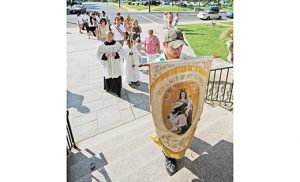 A parishioner carries a banner with an image of Our Lady of Mount Carmel back to church at the end of the annual outdoor procession at Holy Cross Parish, Bridgeton, on July 16. Photo by Alan M. Dumoff
