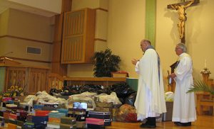 Father Nicholas Dudo, pastor of Our Lady of Perpetual Help, Galloway Township, blesses boxes of donated shoes collected by parishioners. Some will be sent to an orphanage in Haiti. Also pictured is Deacon Michael H. Guerrieri.