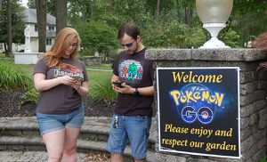 Photo by James A. McBride Alexis Persson and Joe Infanti use their smartphones to play Pokemon Go on the grounds of Saint Charles Borromeo Parish, Sicklerville, on July 30.