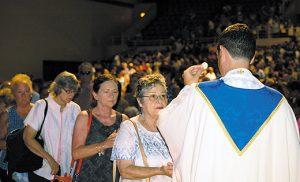 Above, Father Jon Thomas, pastor of Atlantic City's Parish of Saint Monica, distributes Communion. Below, Fathers Fernando Carmona and Thanh Pham, parochial vicars at Saint Monica, during Mass. Photos by James A. McBride