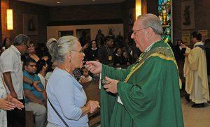 El Obispo Dennis Sullivan distribuye Comunión en la celebración Hispana Católica en la Parroquia Divina Misericordia, Vineland el 18 de septiembre. Foto Alan M. Dumoff