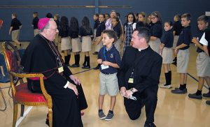 Saint Mary Regional School first grader Patrick McGrory greets Bishop Dennis Sullivan during the Camden leader's visit to the Vineland school on Sept. 7, the second day of classes. Pictured at right is Father Michael M. Romano, secretary to the bishop. Photo by James A. McBride