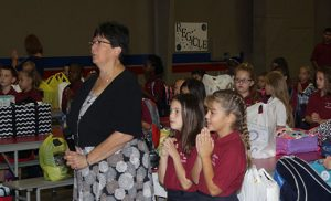 Pictured are students of Saint Michael the Archangel Regional School, Clayton, on the first day back to school, Sept. 6. In the above photo, Janice Bruni, principal, leads students in prayer; in the photo below, third grade students smile for the camera as they wait for the bell to ring. Photos by Mike Walsh