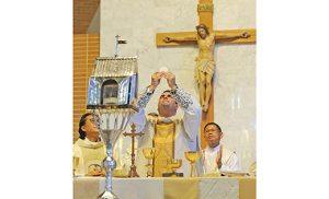 Father Robert Sinatra, pastor of Saint Padre Pio Parish, consecrates the host during a Mass Sept. 25 at Our Lady of Pompeii Church, as the relic heart of the parish's namesake rests in a reliquary in front of the altar. With Father Sinatra are Father Francis Kim, parochial vicar, and Deacon Cesar Sarmiento of Newark. Thousands flocked to Our Lady of Pompeii last weekend to venerate the heart of Saint Pio of Pietrelcina, known for his mercy and love of Jesus and the Blessed Mother. Photo by Alan M. Dumoff
