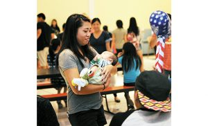 Kathy Nguyen holds a baby at the Mid-Autumn Festival, the second largest holiday in Vietnam, that was held at Most Precious Blood Parish, West Collingswood, on Sept. 17. To communicate authentic church teaching on the sanctity of human life and the evil of abortion, the New Jersey bishops have commissioned an ad campaign. Photo by Alan M. Dumoff