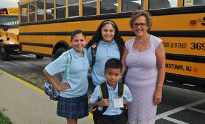 Standing in front of the buses at Saint Mary School, Williamstown, are principal Patricia Mancuso, fifth grader Nola Byrne, seventh grader Keeley Byrne and first grader Alexander Cunanan.