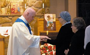 Father Robert Hughes, Vicar General of the Diocese of Camden, anoints the hands of a woman during a Mass of hope, thanksgiving and remembrance for those affected by cancer. Father Hughes was the principal celebrant of the Mass at the Church of the Holy Family in Sewell on Oct. 4. October is Cancer Awareness Month. Photo by James A. McBride