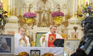 Father Kristof Wtorek, administrator, says Mass to celebrate 1,050 years of Catholicism in Poland at Saint Joseph Church, South Camden, on Oct. 23. Assisting Father Wtorek is Deacon Alfred Niczyporowicz.