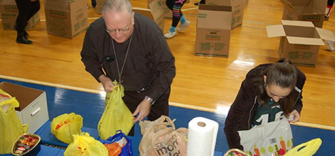 Bishop Sullivan joins student assembly line to pack donations