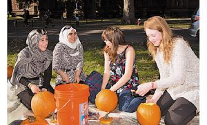 Princeton students and 25 refugee youths now living in New Jersey recently spent a sunny afternoon on campus carving pumpkins before Halloween. The event was co-organized by Princeton's Office of Religious Life and Catholic Charities in Camden. From left, Syrian refugees Rahaf and Reem get to know Princeton sophomores Stephanie Ward and Lilly Chadwick as they carve pumpkins on the lawn in front of Murray Dodge Hall. Photo by Denise Applewhite, Office of Communications